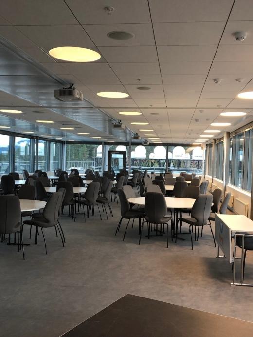 Stor konferansesal med store vinduer, utstyrt med innvendig og utvendige persienner.